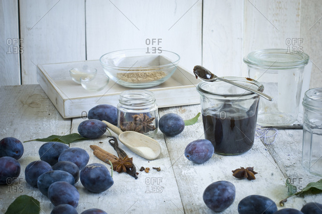 Preserving jar of plum jam and ingredients on wood