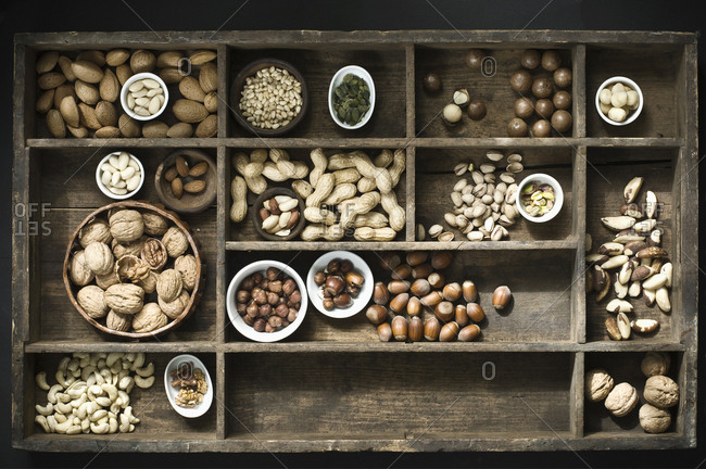 Various peeled an unpeeled nuts in in a type case