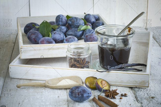 Preserving jar of plum jam- plums  and ingredients on wood