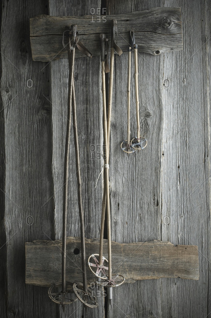 Old ski poles hanging on rustic wooden wall