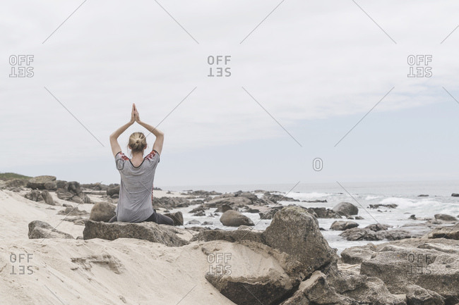 Portugal- Viana do Castelo- back view of woman doing yoga exercise at the sea