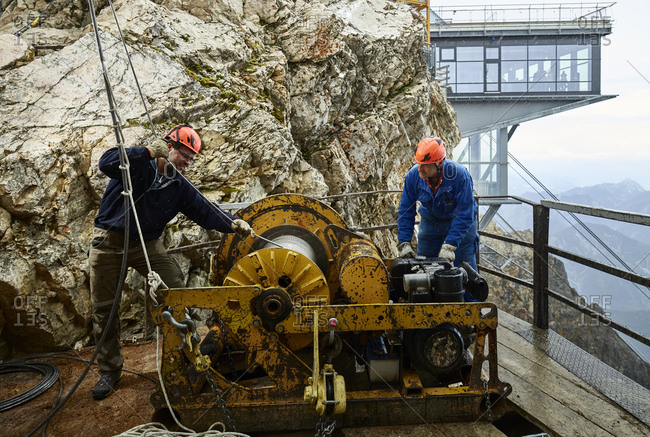 Germany- Bavaria- Garmisch-Partenkirchen- Zugspitze- installers working with rope pulley on goods cable lift