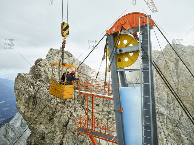 Germany- Bavaria- Garmisch-Partenkirchen- Zugspitze- installers working on goods cable lift in a work cage