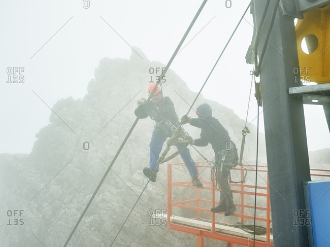 Germany- Bavaria- Garmisch-Partenkirchen- Zugspitze- installers working on steel rope of a goods cable lift