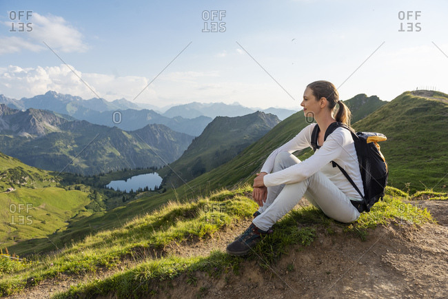 Germany- Bavaria- Oberstdorf- woman on a hike in the mountains having a break