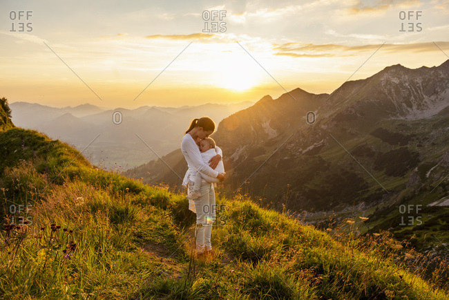 Germany- Bavaria- Oberstdorf- mother holding little daughter on a hike in the mountains at sunset