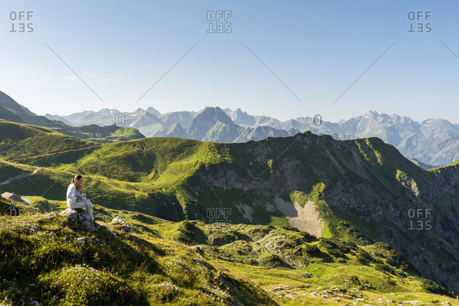 Germany- Bavaria- Oberstdorf- mother and little daughter on a hike in the mountains having a break looking at view