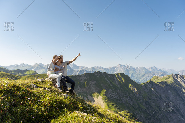 Germany- Bavaria- Oberstdorf- family with little daughter on a hike in the mountains having a break looking at view