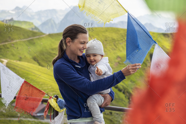 Germany- Bavaria- Oberstdorf- happy mother carrying little daughter on a mountain hut surrounded by pennants