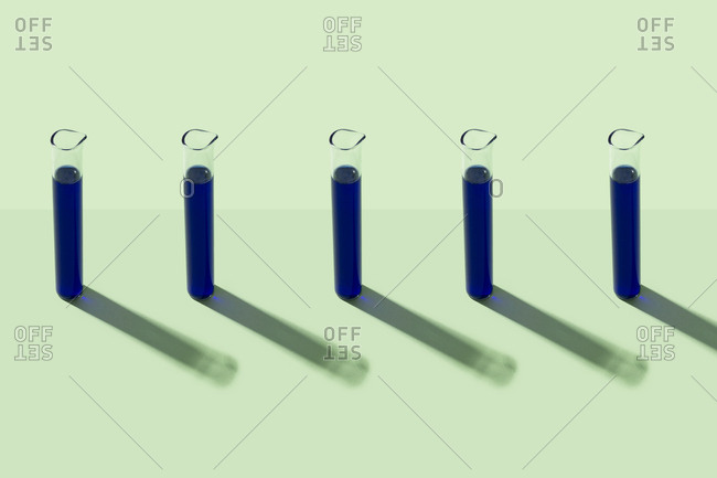 Row of test tubes with blue liquid- green background