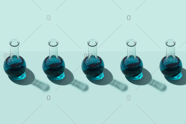 Row of test tubes with liquid- cyan background