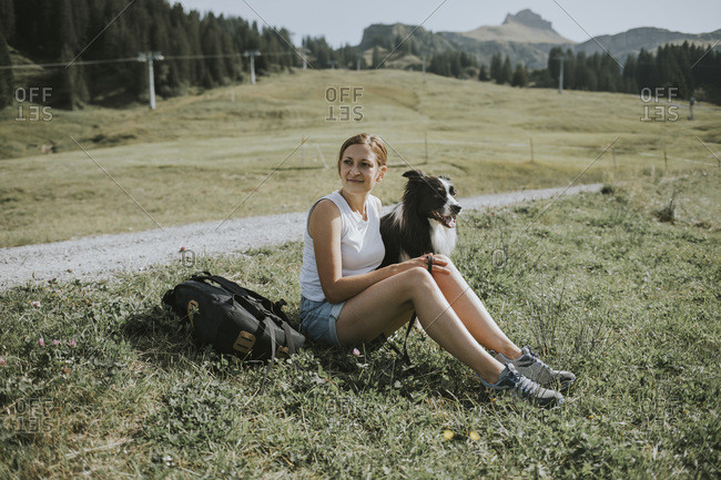 Austria- Vorarlberg- Mellau- woman with dog on a trip in the mountains