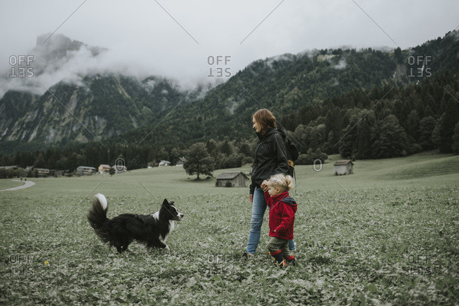 Austria- Vorarlberg- Mellau- mother and toddler with dog on a trip in the mountains