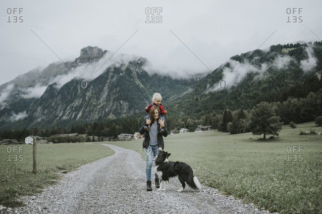 Austria- Vorarlberg- Mellau- mother carrying toddler on shoulders on a trip in the mountains