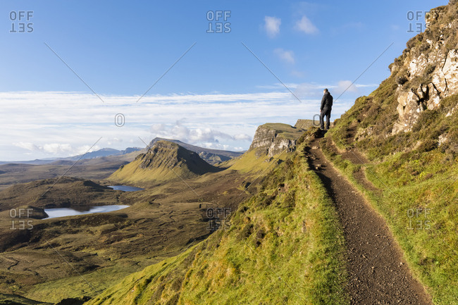 UK- Scotland- Inner Hebrides- Isle of Skye- Trotternish- hiking trail at Quiraing- Loch Cleat- hiker looking at view