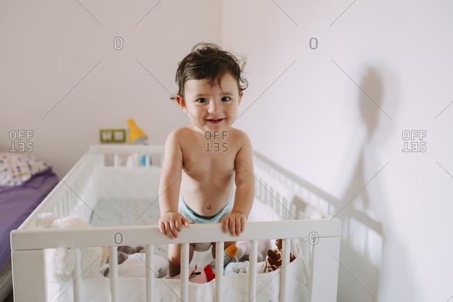 Portrait of happy baby girl in crib