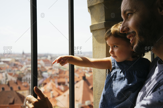 Czechia- Prague- father and little daughter looking together at view from the old town hall