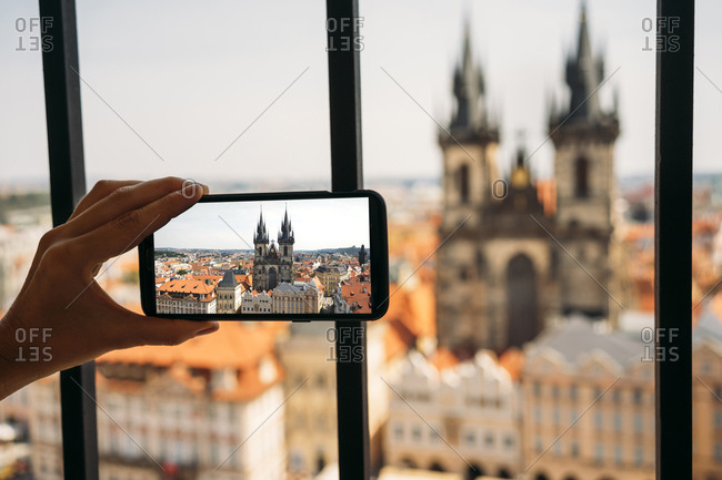 Czechia- Prague- woman taking photo of Church of Our Lady from old town hall with smartphone- partial view