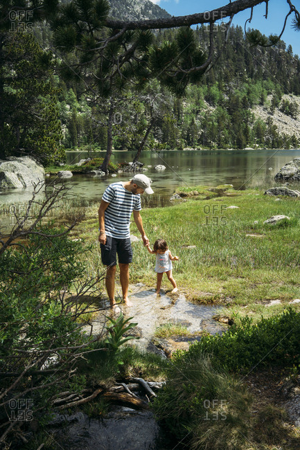 Spain- Father and daughter exploring mountain lake- standing ankle deep in water