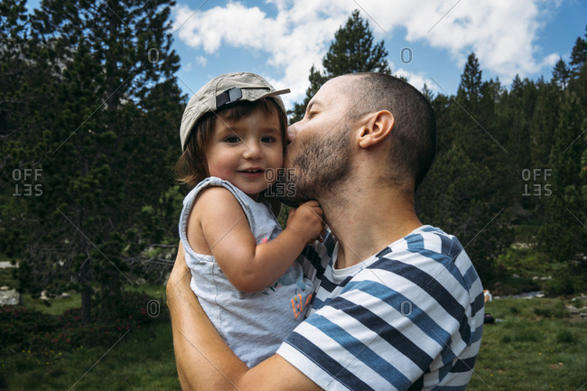 Spain- Father hugging and kissing his little daughter in nature