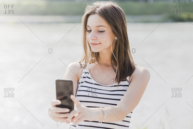 Smiling young woman with smartphone and earphones at the waterfront