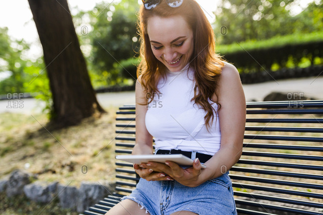 Laughing redheaded woman sitting on bench in park using digital tablet