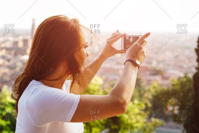 Italy- Verona- Italy- Verona- redheaded woman taking photo with smartphone by sunset
