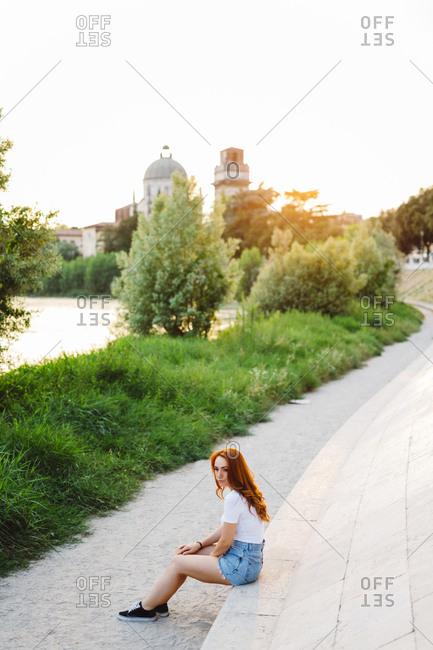 Italy- Verona- redheaded woman realigning at evening twilight