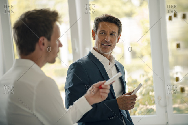 Mature businessman sharing his knowledge with younger colleague