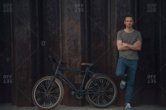 Man leaning against metal wall with arms crossed by bicycle