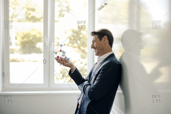 Successful businessman leaning on whiteboard- holding molecule model