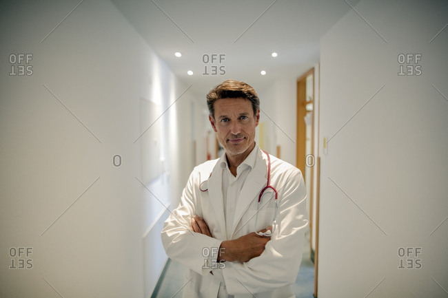 Doctor standing in hospital with arms crossed-  portrait