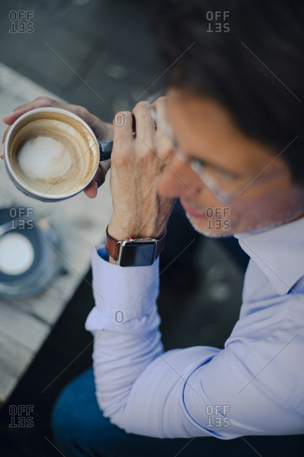 Mature businessman sitting in coffee shop- wearing smart watch