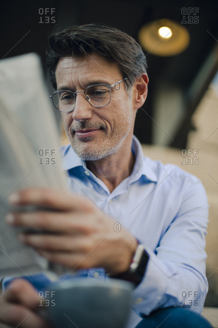 Businessman sitting in coffee shop- reading newspaper- drinking coffee