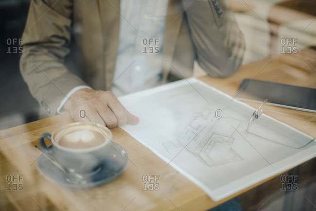 Mature businessman sitting in coffee shop- looking at blueprint