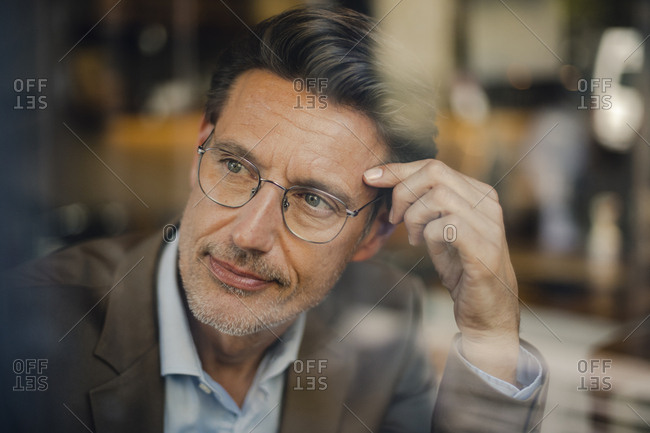 Mature businessman sitting in coffee shop- looking out of window