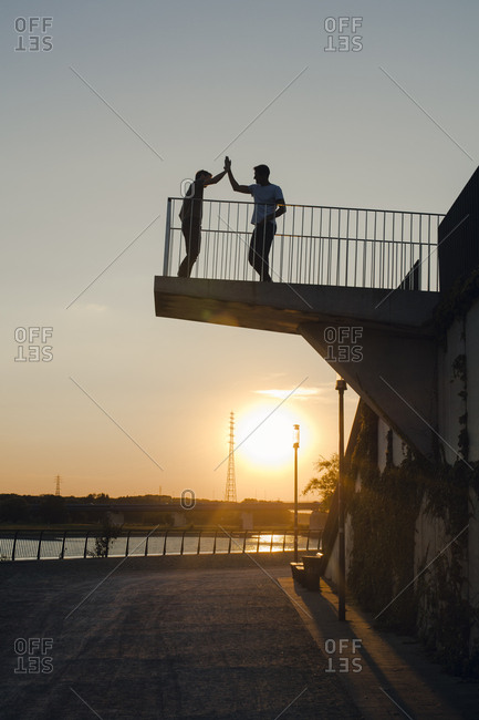 Two friends high-fiving at sunset- standing on observation platform