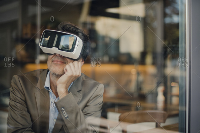 Mature businessman sitting in coffee shop- looking through VR glasses