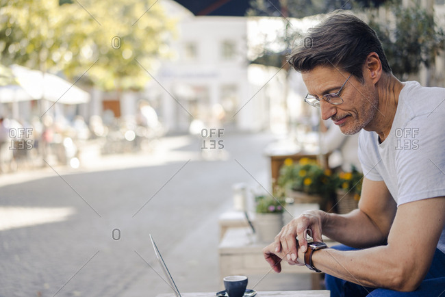Mature businessman sitting in coffee shop- checking time