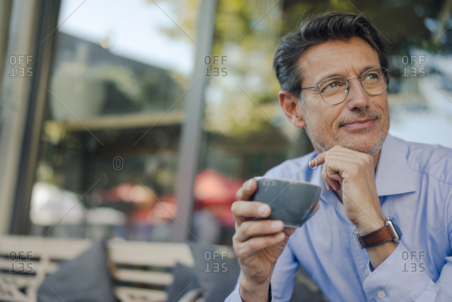 Mature businessman sitting in coffee shop- drinking coffee