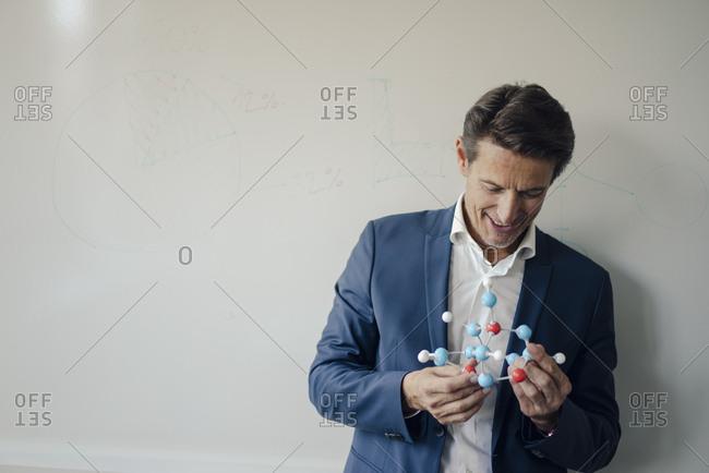 Successful businessman leaning on whiteboard- holding molecule model