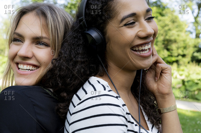 Two girlfriends in a park listening music- laughing- having fun