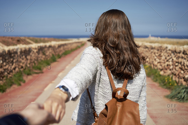 Cheerful young brunette woman holding hand of man