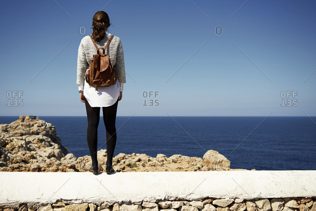 Young brunette woman standing on wall- looking at view