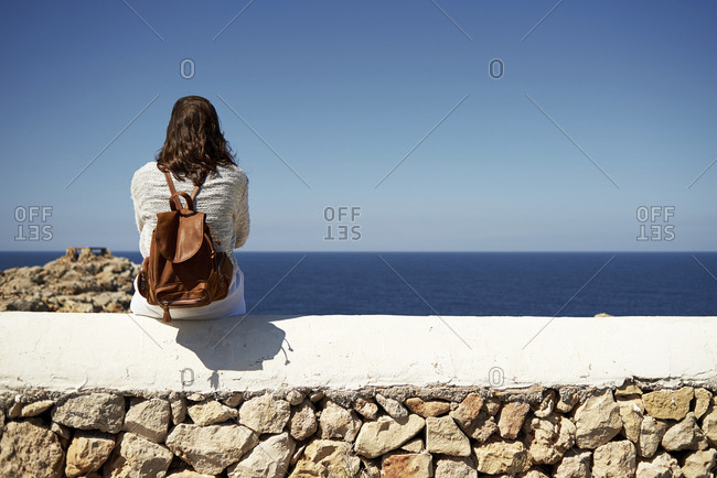 Young brunette woman sitting on wall- looking at view