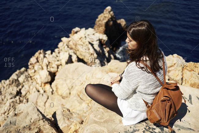 Young brunette woman sitting on coast- looking at view