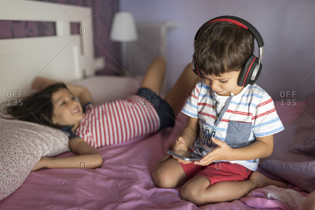 Little boy listening music with oversized headphones on bed while his sister relaxing in the background