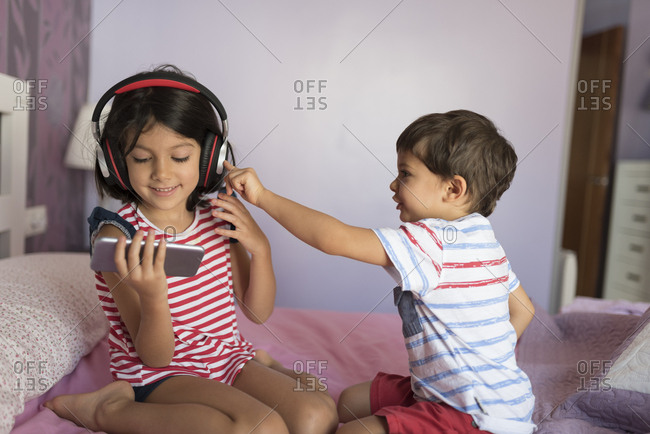 Portrait of smiling girl listening music with headphones while her little brother disturbing her