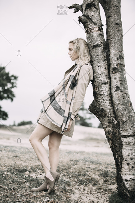 Fashionable young woman wearing coat and scarf leaning against tree trunk