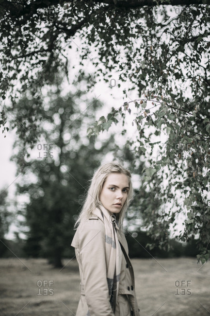 Portrait of fashionable young woman wearing coat and scarf in nature